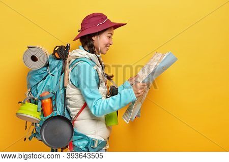 Sideways Shot Of Asian Female Tourist Studies Map, Finds New Destination To Explore, Travels Alone,
