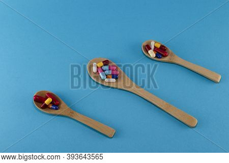Close-up Of Pills In Three Wooden Spoons With Blue Background