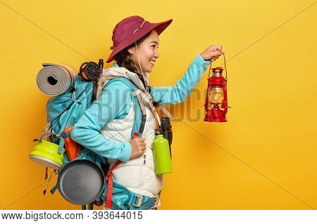 Photo Of Smiling Asian Woman Holds Little Oil Lamp, Going To Explore Place In Darkness, Carries Ruck