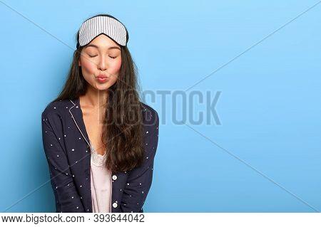 Horizontal View Of Lovely Asian Girl Wears Sleep Mask, Pyjamas, Keeps Lips Rounded, Eyes Shut, Wakes