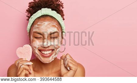 Pretty Smiling Afro Woman With Black Curly Hair, Clenches Fists, Enjoys Relaxing Time, Peels Face Wi
