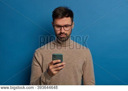 Serious Male Blogger Uses Modern Smartphone, Has Attentive Gaze At Display, Wears Spectacles And Tur