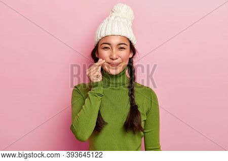 Pretty Adorable Mixed Race Girl Makes Korean Heart Gesture, Has Long Hair Combed In Plaits, Wears Wa