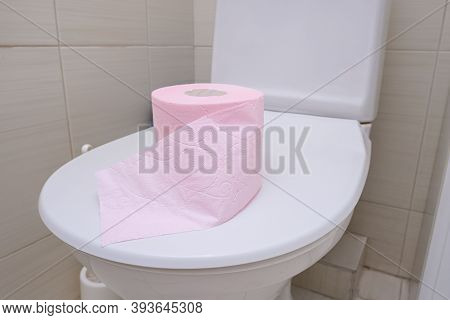 A Pink Piece Of Toilet Paper Standing On A Cover Of A Toilet Bowl, Digestive Problems And Defecation