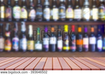 Empty Wooden Counter With Blurred Background Of Many Liquor And Brandy On Shelf Of Wooden Wall Decor