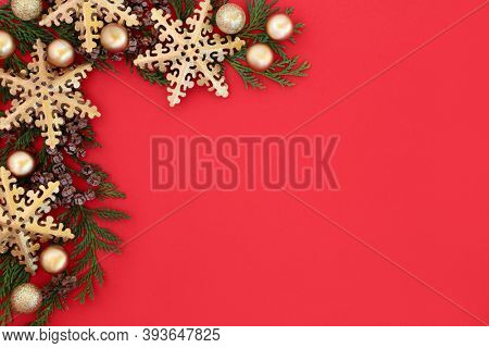 Christmas background border with gold snowflake & ball baubles with cedar cypress winter greenery on red. Festive composition for the holiday season. Flat lay, top view, copy space.