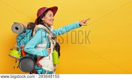 Photo Of Happy Delighted Korean Young Woman Points Into Distance, Carries Rucksack Stands In Profile