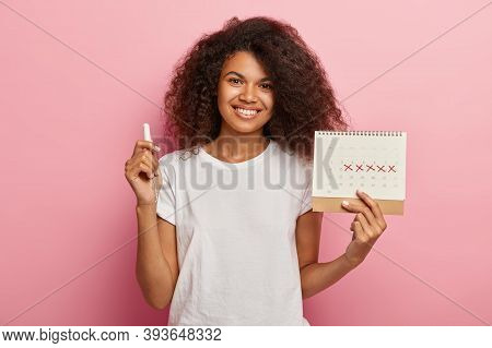 Happy Curly Haired Lady Holds Menstruation Calendar With Marked Pms Days And Tampon, Dressed In Casu