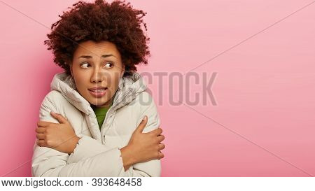 Unhappy Adult Woman Keeps Hands Crossed Over Chest, Trembles From Cold, Wears Winter Clothing, Walk