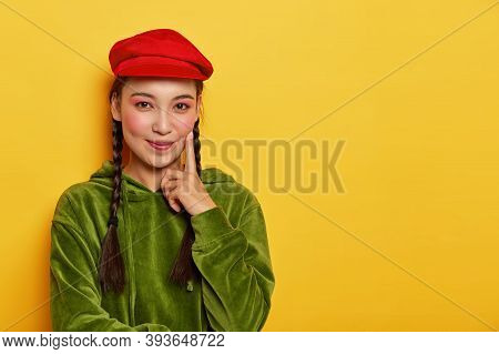 Image Of Lovely Girl With Asian Appearance, Minimal Makeup, Touches Cheek With Index Finger, Looks P