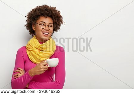 Smiling Glad Dark Skinned Woman Holds Mug With Aromatic Coffee, Has Pleasant Talk During Drinking Te