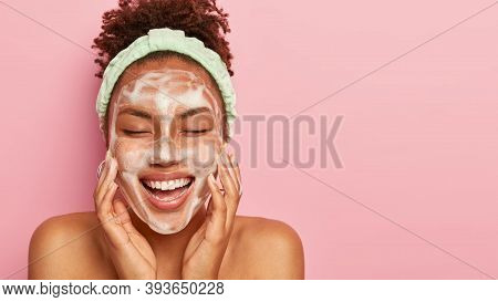 Beautiful Dark Skinned Young Lady Cleans And Washes Face With Foam, Massages Cheeks, Closes Eyes Fro