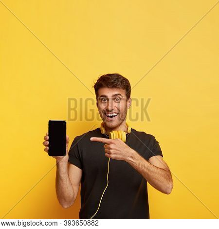 Indoor Shot Of Handsome Happy Youngster Holds Mobile Phone, Points At Display, Shows Mock Up Space F