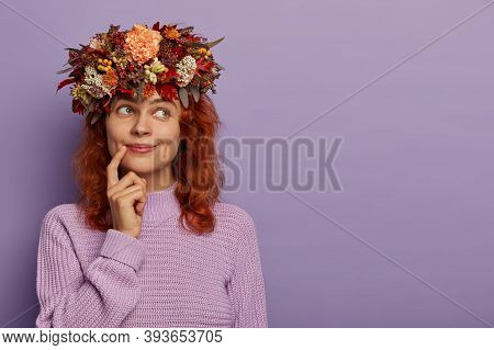 Candid Shot Of Beautiful Redhead Woman Has Dreamy Expression, Keeps Finger Near Lips, Being Deep In