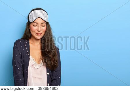 Half Length Shot Of Satisfied Korean Girl Prepares For Sleep In Bedroom, Wears Sleeping Mask, Casual