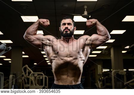 Strong Male Physique Concept Of Muscular Young Bearded Handsome Man Showing Muscles Biceps In Fitnes