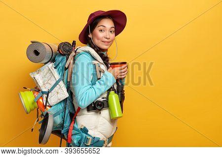 Indoor Shot Of Female Traveler Has Coffee Break, Enjoys Trip, Carries Rucksack With Necessary Things