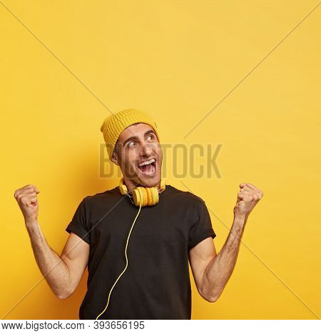 Overjoyed Man Raises Clenched Fists, Feels Energized And Upbeat, Wears Yellow Hat And Black T Shirt,