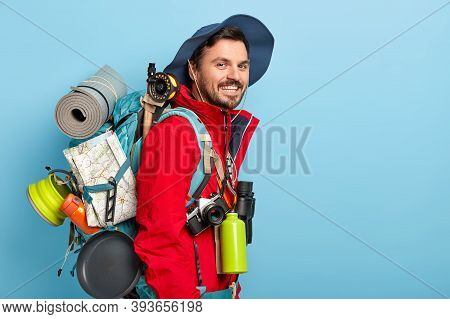 Profile Shot Of Smiling Caucasian Male Tourist Wears Hat And Red Jacket, Carries Rucksack With Map,