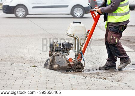 A Worker Cuts The Old Asphalt With A Gas Saw On The Carriageway Against The Backdrop Of A City Stree