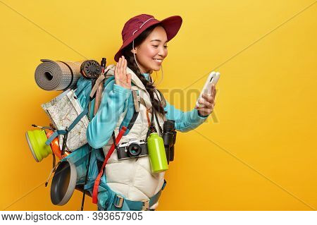 Photo Of Happy Asian Girl Waves Palm, Greets Someone Via Video Call, Holds Mobile Phone In Hand, Car