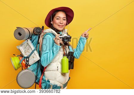 Active Female Backpacker Points Index Finger On Copy Space Aside, Holds Retro Camera, Takes Pictures