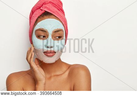 People, Beauty, Self Care Concept. Thoughtful Dark Skinned Woman Touches Cheek, Applies Clay Mask An