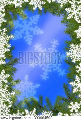Christmas frame made of fir tree branches and white snowflakes on blue background