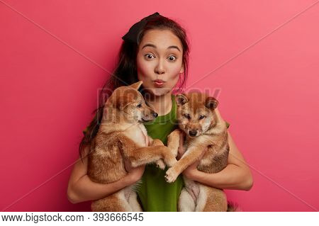 Surprised Asian Lady Keeps Lips Folded, Poses With Two Puppies, Carries To Vet Clinic. Pretty Female