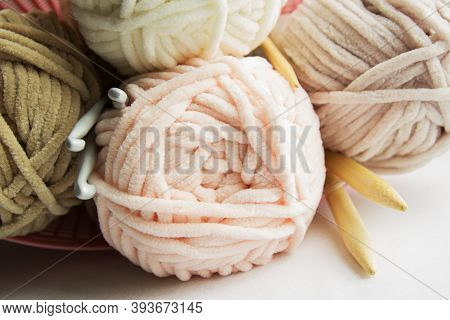 Skewers Of Plush Yarn Pastel Tones With Spokes And Hooks On A White Table.