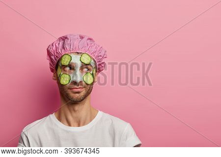 Photo Of Male Model Concentrated Aside, Has Beauty Procedures, Applies Clay Mask And Cucumbers On Co