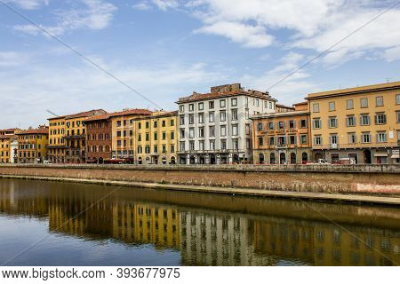 Pisa, Italy - July 8, 2017: View Of Traditional Old Buildings And Tourists Walking By The Arno River