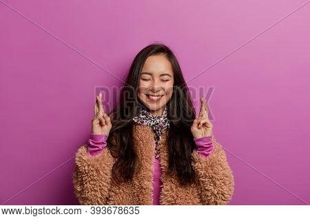 Glad Adorable Asian Woman Waits For Special Moment, Keeps Fingers Crossed, Prays For Better, Smiles