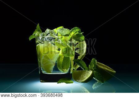 Cocktail With Lime , Ice  And Peppermint Leaves On A Glass Table In Bar. Black Background .
