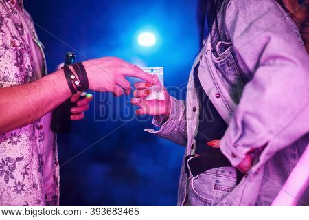 Young Girl Buying Drugs Inside Of Night Club At Party Time.