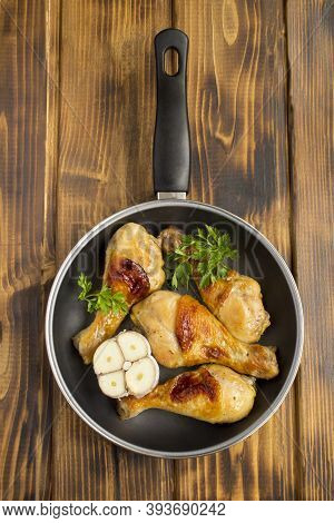Top View Of Fried Chicken Legs In The Frying Pan On The Wooden Background. Location Vertical.