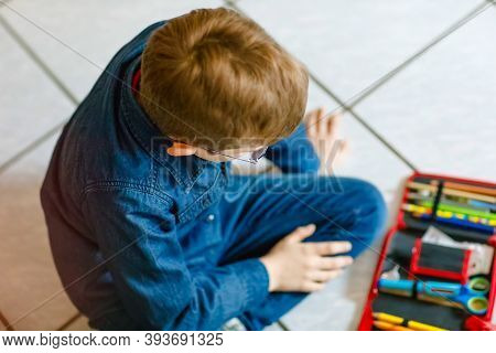 Happy Little School Kid Boy Searching For A Pen In Pencil Case. Healthy Schoolchild With Glasses Gra