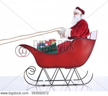 Santa Claus sitting in hi sleigh holidng onto the reins, with a sack of presents at his feet. Isolated on white.