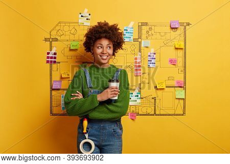 Repair, Building And Home Renovation Concept. Satisfied Dark Skinned Woman Stands With Takeaway Coff
