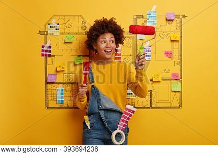 Shot Of Glad Curly Haired Afro American Woman Painter Looks Happily At Paint Roller, Holds Brush Pai