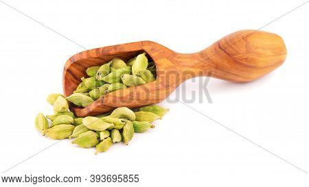 Cardamom Seeds In Wooden Scoop, Isolated On White Background. Pile Of Green Cardamom Pods.