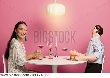 Horizontal Shot Of Woman And Inflated Doll Man Have Dinner Together With Candle, Drink Cocktail, Pre