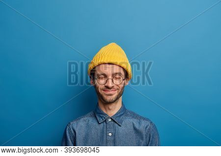 Optimistic Caucaisan Man Keeps Eyes Closed, Smiles Happily, Wears Yellow Headgear And Denim Shirt, H