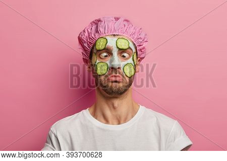 Young Man Crosses Eyes, Applies Cream Mask On Face With Cucumber, Has Beauty Session, Wears Bath Cap