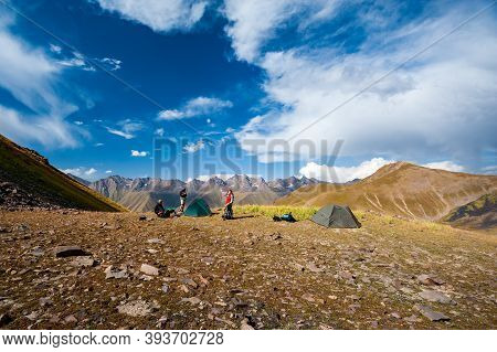 Group Of Trekkers Camping In Mountain Pass. Climbers Pitch Tent In Nature Near Sary Chelek Lake, Sar