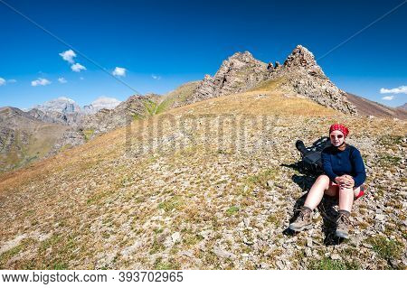 Young Trekker Woman Resting In Rocky Pass With Mountain Top Wiews In High Mountains. Woman With Sun