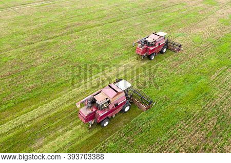 Agriculture Industry. Aerial View Of Two Red Harvester. Harvesters Works In Field. Harvest Of Crops.