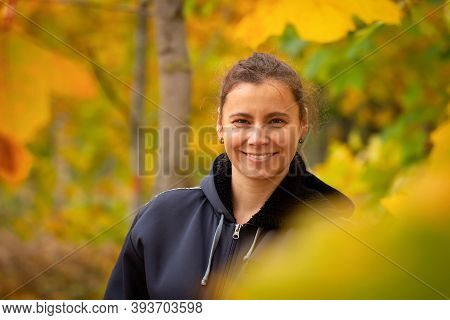 Portrait Smiling Young Woman. Woman Among Yellow Leaves. Woman Walking In Autumn Park.