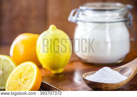 Glass Pot With Baking Soda And Wooden Measuring Spoon, With Fruits In The Background, Lemon And Oran