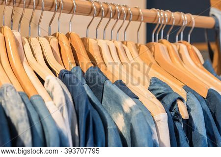 Clothes On Wooden Hangers In Shelf Fashion For Sale Shopfront Store Collection For Customer Or Shopp